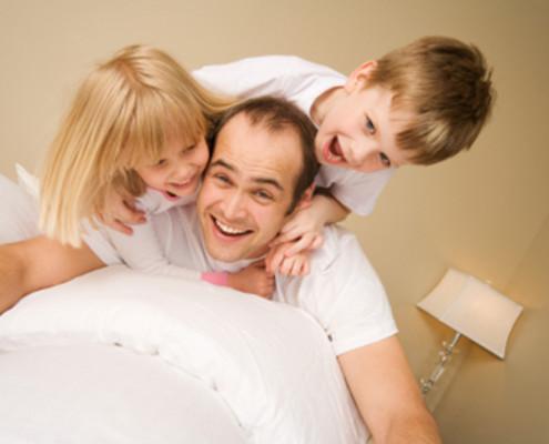 Familie spielt in Bett - München